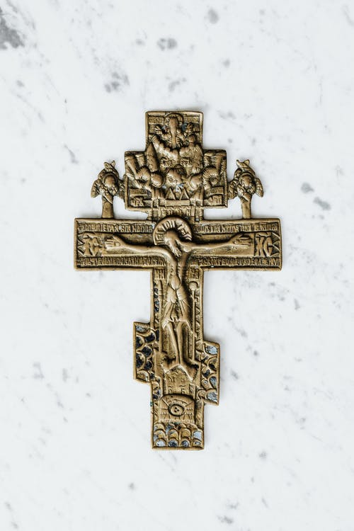 Gold Cross on White Surface