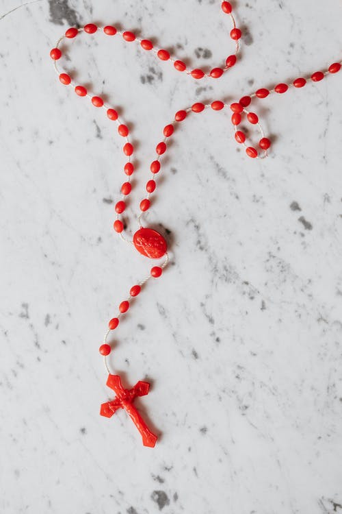 Red Rosary on White Surface