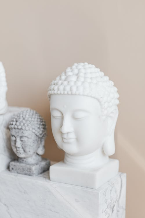 Tibetan marble busts of Buddha on beige background
