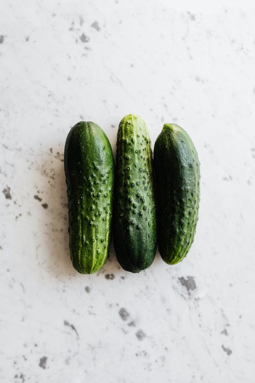 3 Green Cucumbers on White Surface