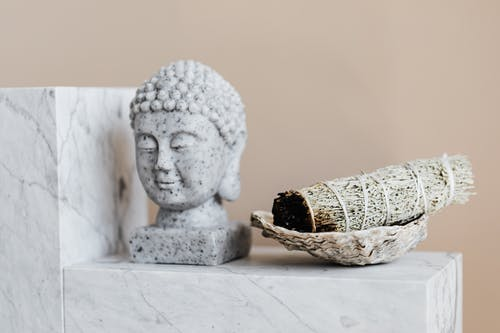 Bust of Buddha and dry sage bundle on marble surface