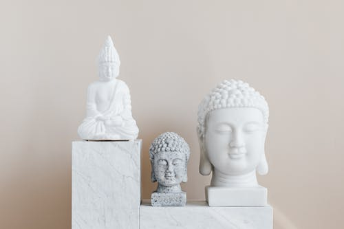 Decorative statue and busts of Buddha on beige background