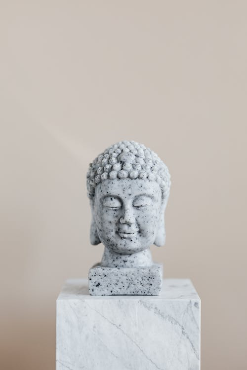 Stone bust of Buddha on marble stand