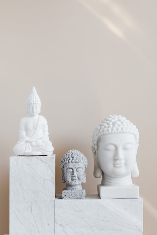 Set of various gypsum and stone Buddha sculptures placed on white marble shelf against beige wall as home decoration element and religion symbol