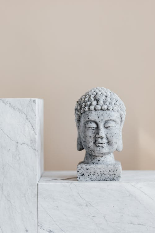 Granite statue of Buddha placed on white marble shelf against beige wall as religion symbol and home decoration element