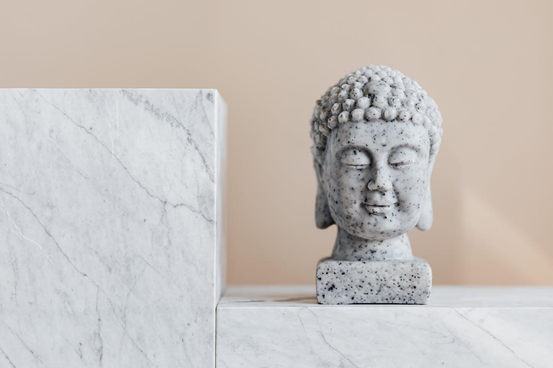 Traditional stone Buddha statue on marble shelf