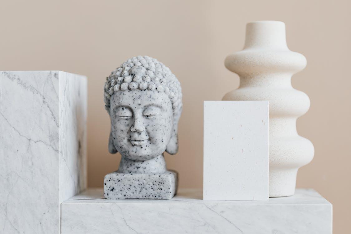 Granite bust of Buddha placed near white ceramic vase of creative geometric shape and blank card on white marble shelf against beige wall