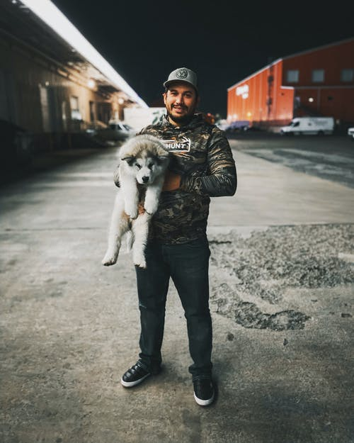 Photo of Man Standing While Carrying His Dog