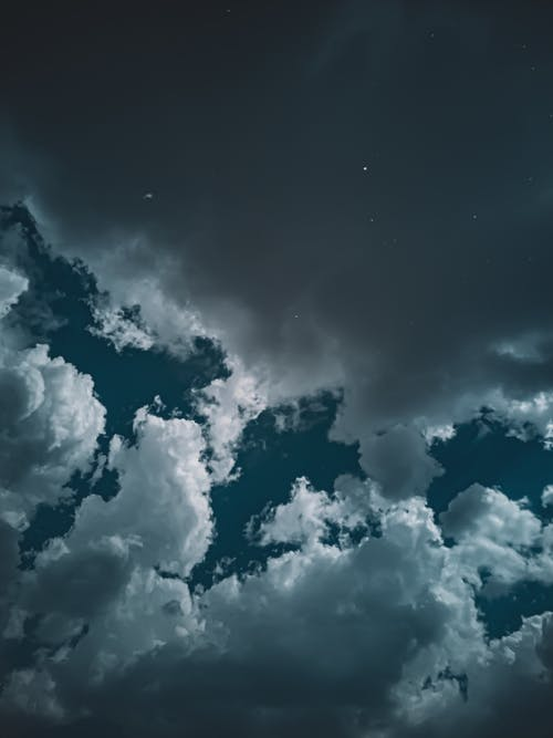 From below of dark blue sky with gray and white fluffy clouds at night
