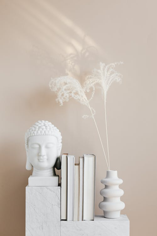 Vase with dried herbs arranged with Buddha bust and books