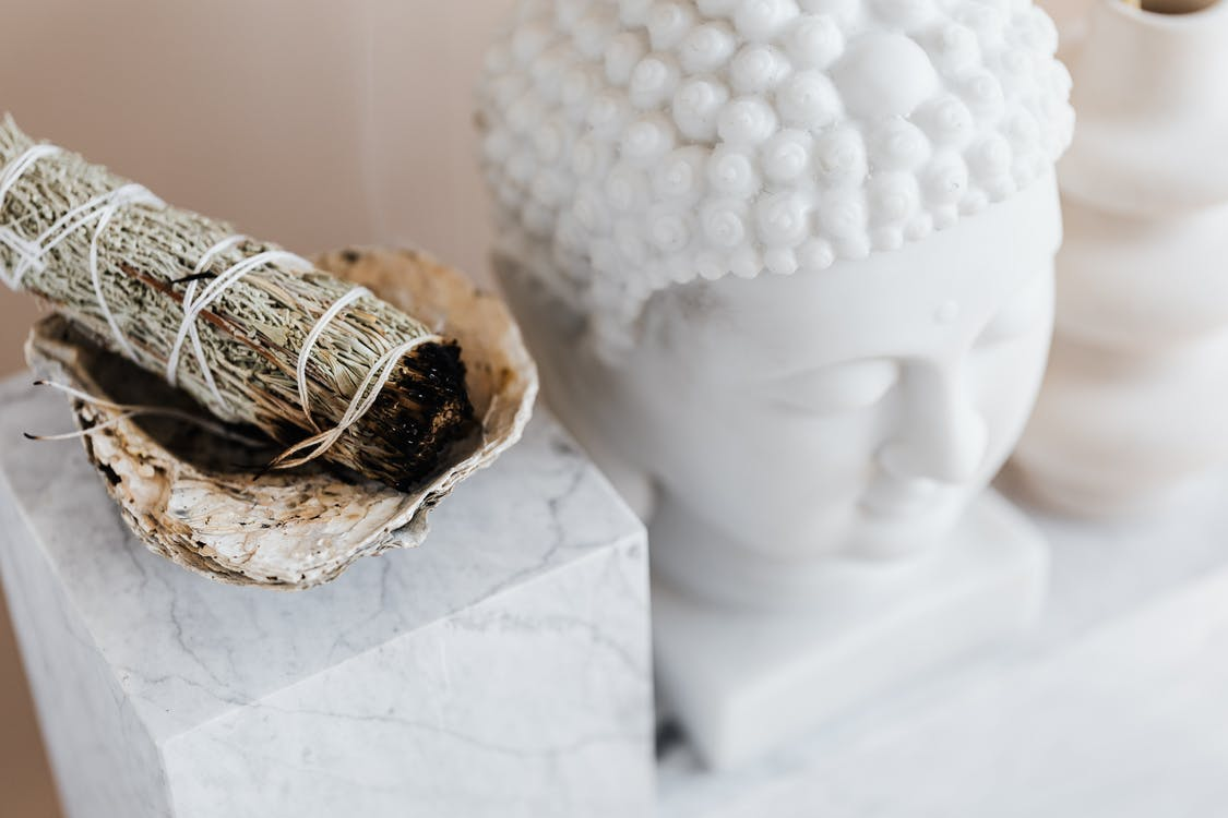 From above of sage candle in bowl placed on white marble shelf near plaster Buddha bust and creative shape vase for home decoration