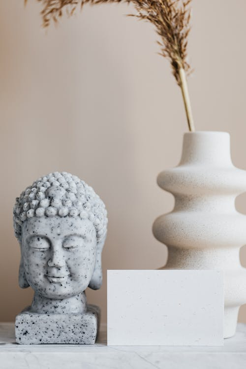 Vase with dried herb arranged with Buddha bust and blank card