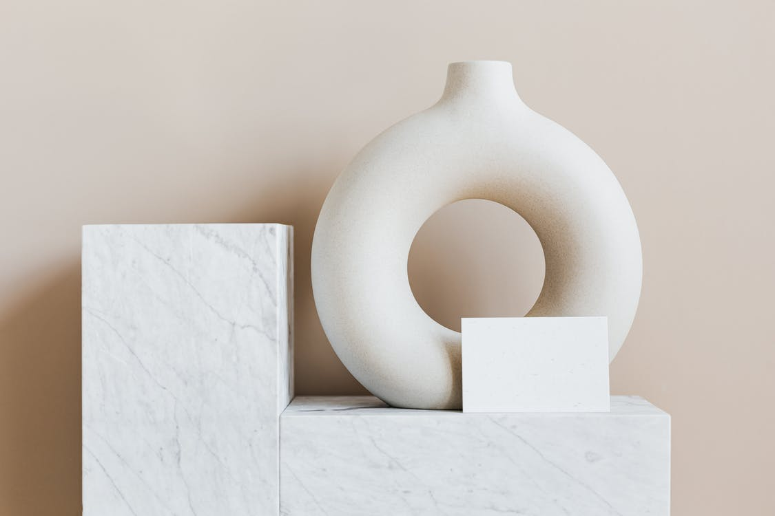 Composition of creative white ceramic vase in ring shape with empty postcard placed on white marble shelf against beige wall as home decoration elements or art objects