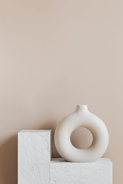 Decorative vase of ring shape on marble stand