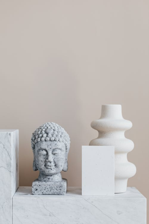 Home decoration composition with stone Buddha sculpture and creative ceramic vase