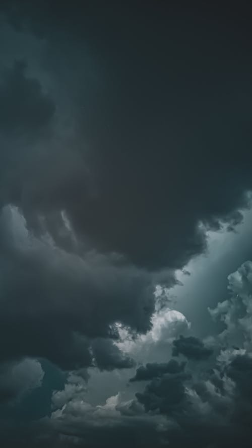 Abstract fluffy clouds of gray and black color high in dark sky in overcast