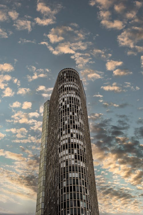 Photo of High-Rise Building Under White Clouds