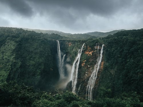 Waterfalls in the Middle of Green Trees Under Gray Clouds