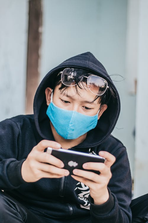 Person Wearing Black Hoodie and Blue Face Mask While Using Smartphone