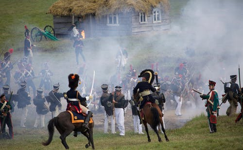 Horse mounted officers and soldiers with rifles and muskets fighting on field in countryside during reenactment of Napoleonic war