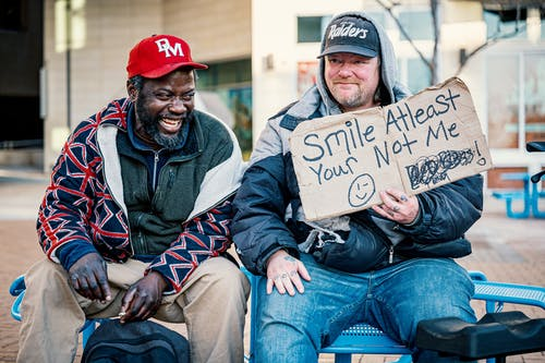 Happy diverse men having fun on street bench