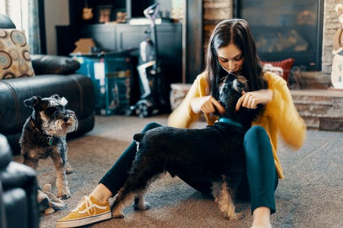 Photo of Woman Sitting on Floor While Kissing Her Dog