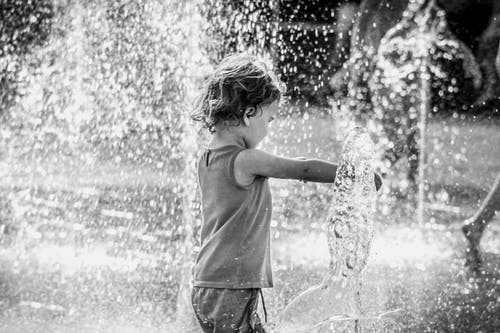 Grayscale Photo of Child Playing in Water Fountain