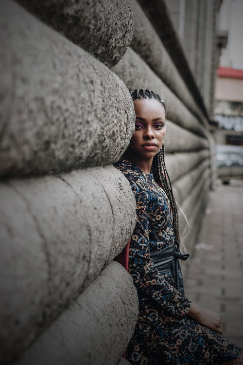 Side view of calm young ethnic lady with Afro braids in casual clothes leaning on wall of aged stone building while resting on street