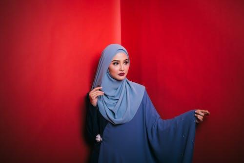 Elegant young Muslim lady looking away in red studio