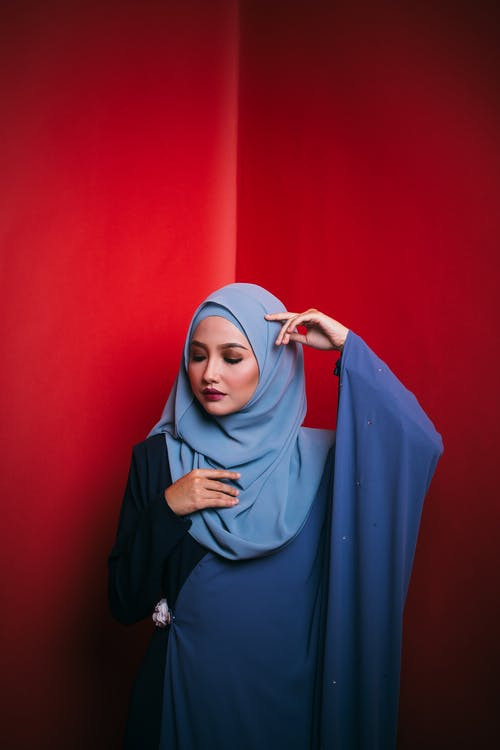 Woman in Blue Hijab Standing Beside Red Wall