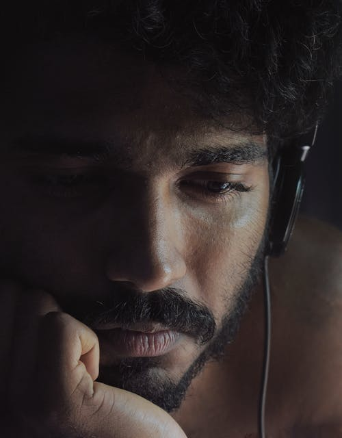 Close-Up Photo of Man Looking Sad While Wearing Black Headphones
