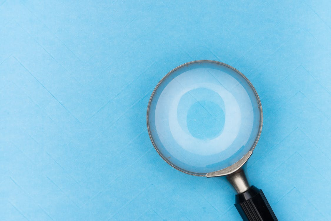 Black Magnifying Glass on White Table