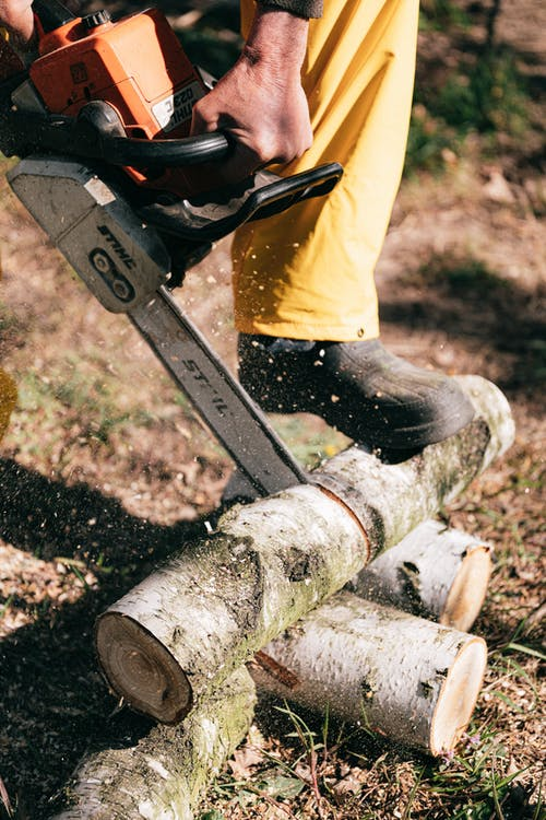Person Cutting Wooden Logs Using Chainsaw