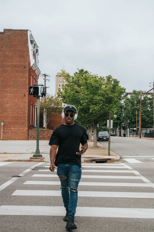 Man in Black Crew Neck T-shirt and Blue Denim Jeans Crossing the Street