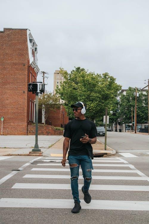 Man in Black Crew Neck T-shirt and Blue Denim Jeans Crossing on Pedestrian Lane