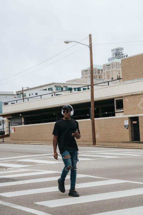 Photo of Man Wearing Black Shirt and Denim Jeans While Walking on Pedestrian Lane