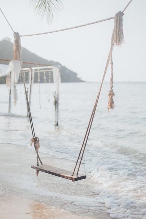Brown Wooden Swing on Beach