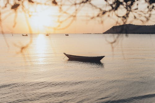 White and Black Boat on Sea during Sunset