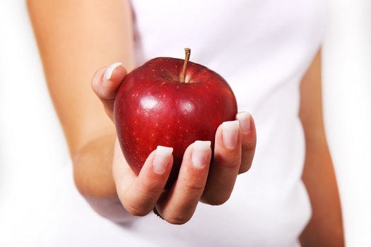 Person in White Shirt Holding Red Apple