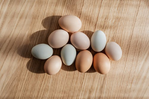 Top view set of organic pastel colored raw chicken eggs placed on wooden table in daylight