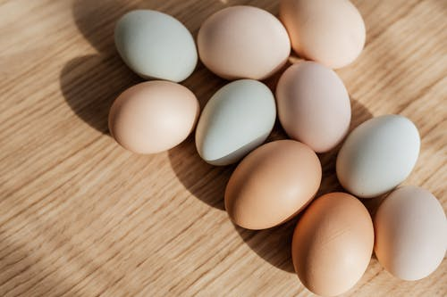From above closeup of raw organic multicolored chicken eggs arranged on wooden surface in daylight