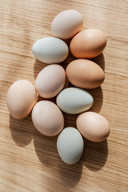 Top view composition of various organic chicken eggs placed on wooden background in daylight
