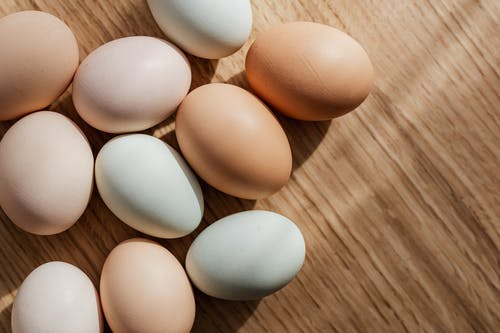 Top view of assorted mixed chicken raw multicolored eggs placed together on wooden surface during daytime