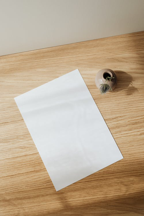 From above composition of empty white paper sheet placed near beige creative ceramic vase with artificial flower on wooden desk against white wall in daytime