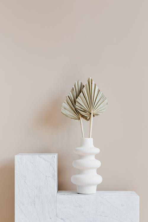 Decorative golden leaves in unique formed white vase placed on marble table against beige background