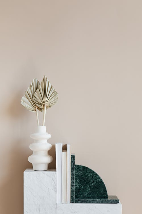 Minimalistic interior design with original vase with decorative golden leaves and set of magazines with green marble bookend placed on white shelf