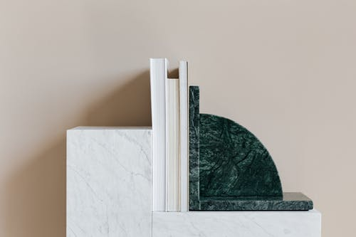 Marble patterned cabinet decorated with stylish bookend and set of magazines