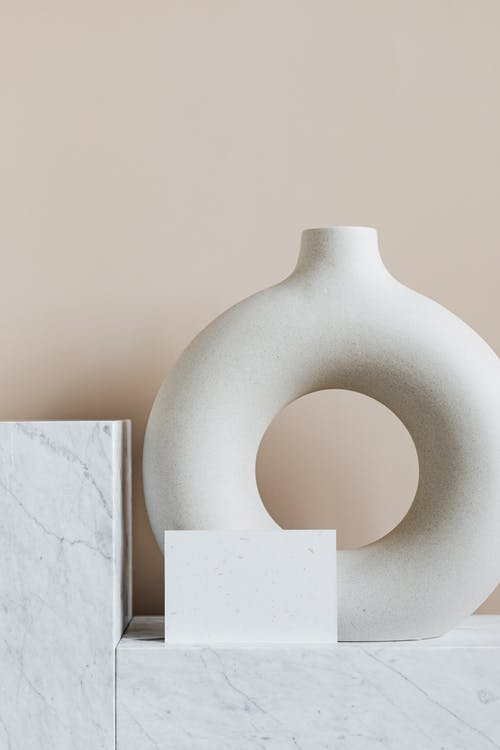 Original circular ceramic vase placed on marble cabinet against beige wall in modern minimalistic apartment