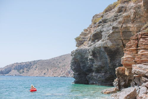 Person in a Kayak on the Sea Near a Rock Formation