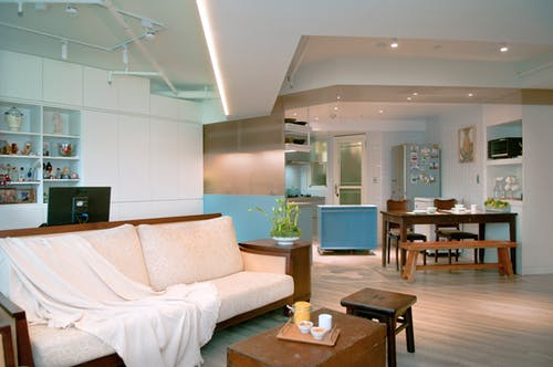 Interior of bright room with table and fridge in kitchen area and sofa in lounge zone decorated in white colors